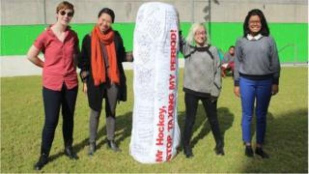Subeta Vimalarajah and fellow campaigners hold up tampon-shaped protest sign