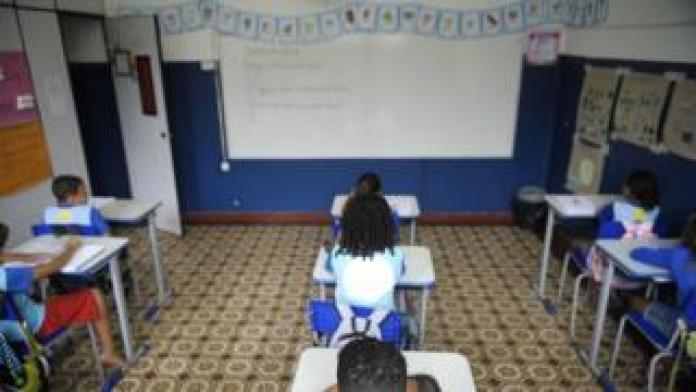 Crianças sentadas enfileiradas em cadeiras em sala de aula