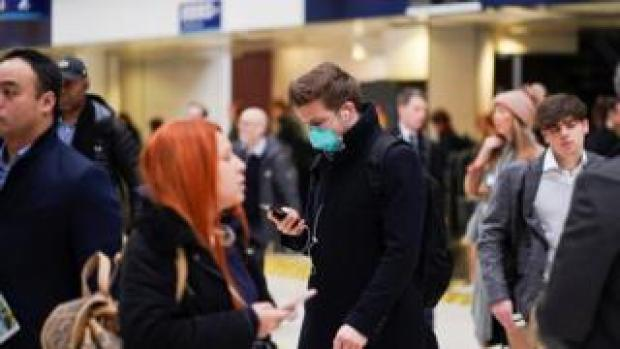 A man wearing protective face mask walks through Waterloo station, as the number of coronavirus cases grow around around the world, in London,