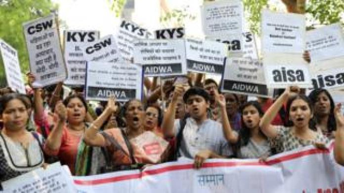 Indian activists hold placards that read in Hindi
