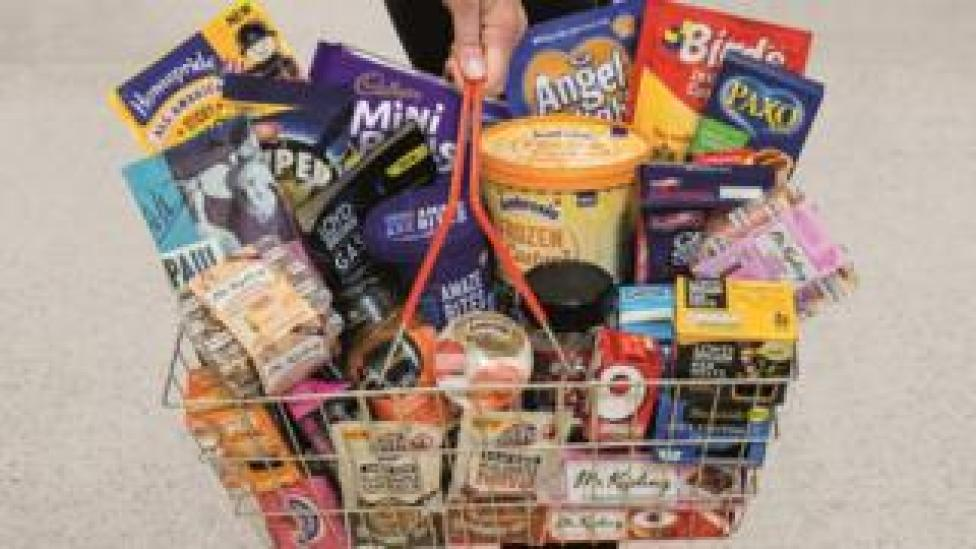 A shopper carries a basket of Premier Food products