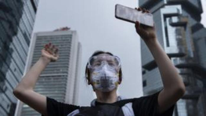A protester holds a mobile phone