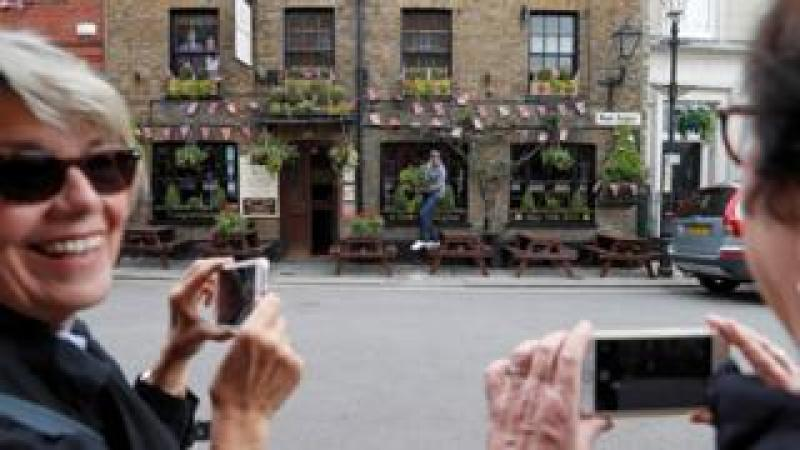 Flowers are hung outside a pub, covered in Union flag-themed bunting near Windsor Castle in Windsor