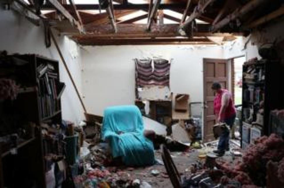 NEWS A Panama City resident begins cleaning her home, which has had the roof blown off.