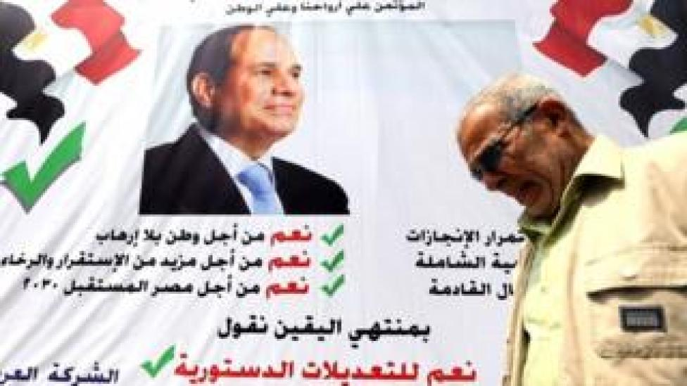 """A man walks in front of a banner reading, """"Yes to the constitutional amendments, for a better future"""", with a photo of the Egyptian President Abdel Fattah al-Sisi before the approaching referendum on constitutional amendments in Cairo, Egypt on 16 April 2019."""