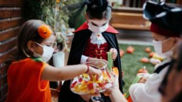 Children trick or treating while wearing masks