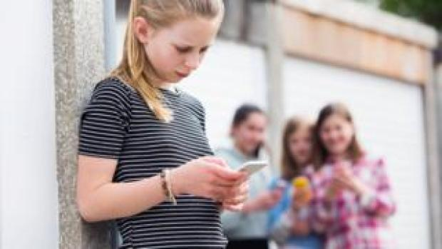 Teenage girl holding a phone being bullied