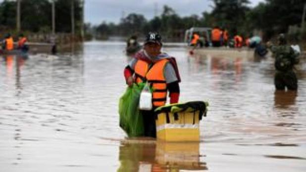 A volunteer wading through a flooded road after the dam collapse in southern Laos