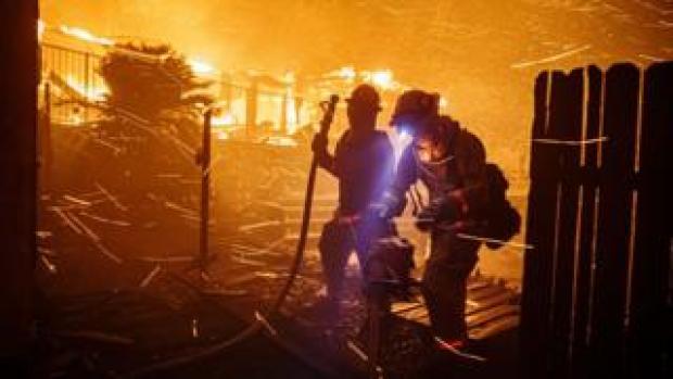 Firefighters work to control the flames in the North Park neighbourhood if San Bernardino, California