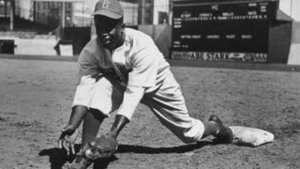 Jackie Robinson grounding a ball in an exhibition game against the New York Yankees in 1950