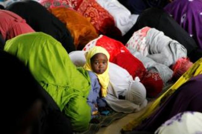 A child is seen among Muslim faithfuls on 5 June attending the morning prayers of Eid al-Fitr, which mark the end of the holy month of Ramadan, at the California grounds in Nairobi.
