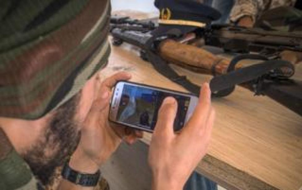 """A fighter loyal to the internationally-recognised Government of National Accord (GNA) play online video game PlayerUnknown""""s Battlegrounds (PUBG) on their phones during a break from fighting, in a military base in Tajoura, south of the Libyan capital Tripoli on May 1,"""