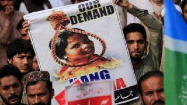 The protester holds a poster with a Bibi head in Asia in a circle above the fire factory