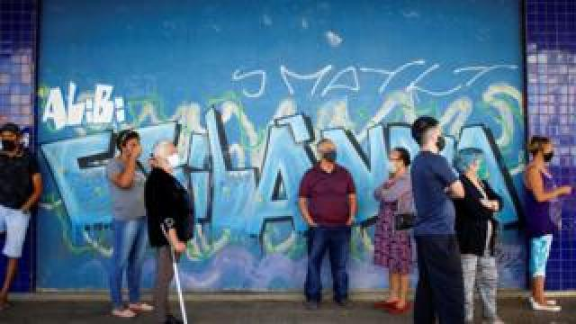 A queue of people wearing face masks in front of a wall covered in graffiti in Brasilia, Brazil