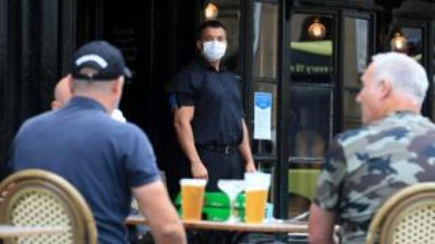 A doorman wearing PPE (personal protective equipment), of a face mask or covering as a precautionary measure against spreading COVID-19, stands on duty as customers sit with their drinks at a re-opened pub in Newcastle