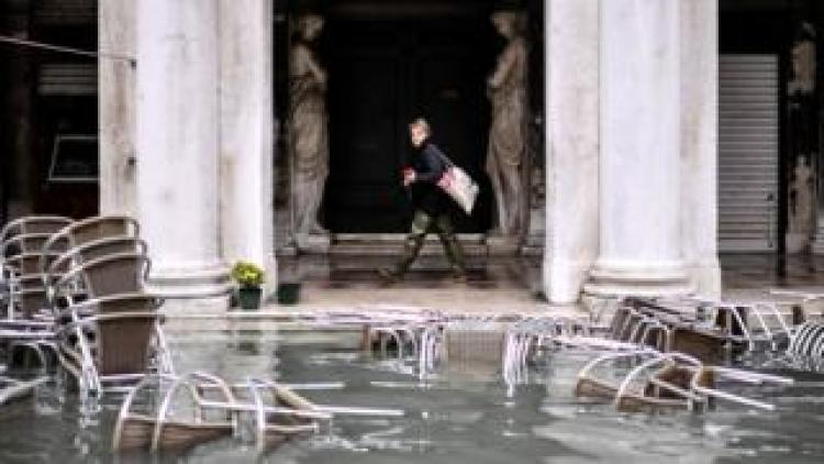 A woman walks past flooded furniture of a cafe terrace as Venice suffers in extremely high water levels, 13 November 2019