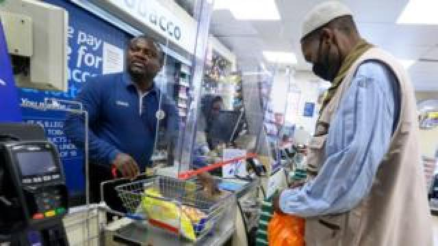 Staff and customer at Tesco store