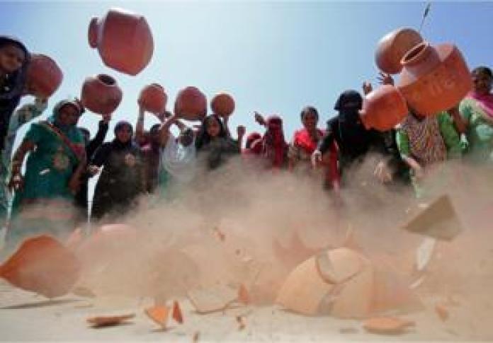 Women throw earthen pitchers onto the ground