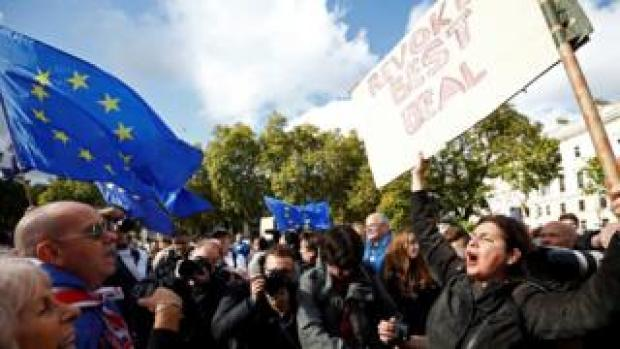 A crowd faces off, with EU and UK flags visible, while an anti-Brexit campaigner waves as sign demanding Brexit be stopped
