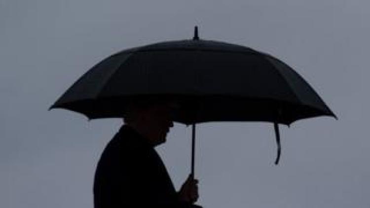 Trump under umbrella