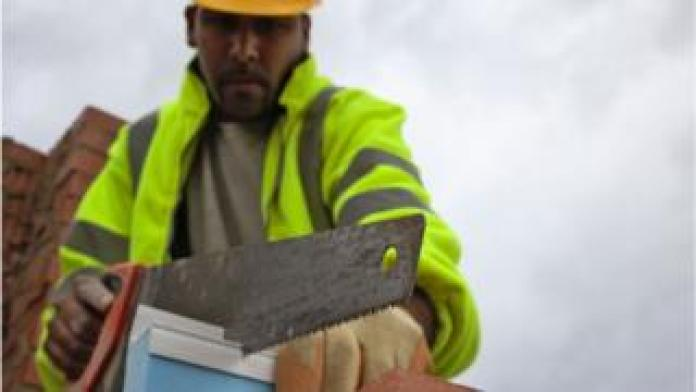 A worker cuts insulation