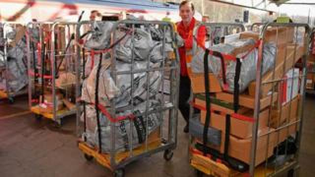 Royal Mail worker pushes a trolley of parcels
