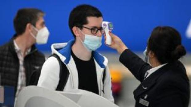 Passengers wearing face masks or covering due to the Covid-19 pandemic, have their temperature taken as they queue at a British Airways check-in desk at Heathrow airport.