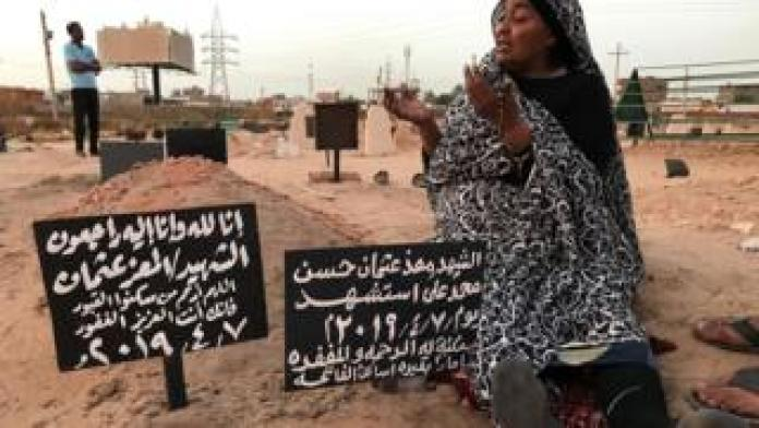 Khadom, the mother of Al-Moez visits the tomb of her son, killed when a bullet pierced the window of his workplace and lodged itself in his heart during an anti-government demonstration in the Sudanese capital Khartoum in April, on July 9, 2019. - Like dozens of others who lost a son, uncle or brother, Al-Moez' family has paid a high price for Sudan's revolution that toppled its longtime autocratic ruler Omar al-Bashir in April.