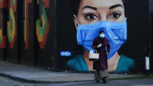 A woman wearing a mask walks in front of a mural of an NHS worker