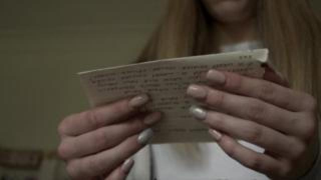 Anonymous woman whose mother was imprisoned reading a letter
