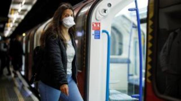 A person getting on the tube with a face covering on