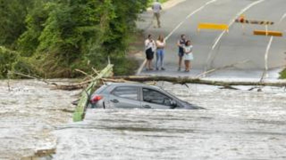A car is submerged in flood waters on a road near Bega in NSW