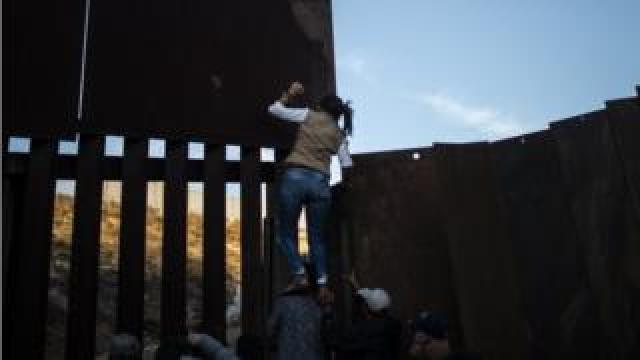 Central American migrants climb the metal barrier separating Mexico and the US on 2 December, 2018