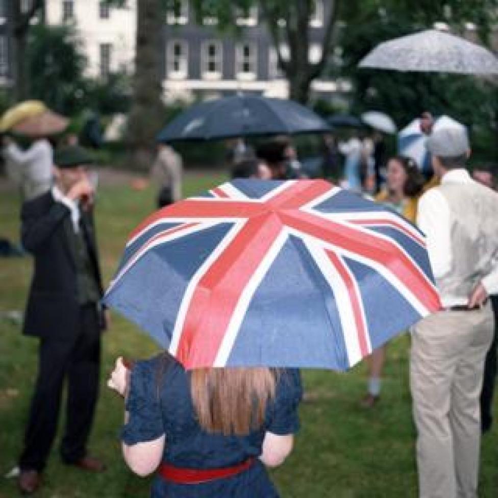 A woman holding a Union Jack umbrella