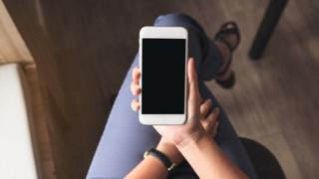 A woman holds a smart phone