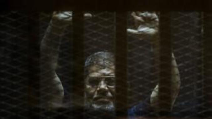Ousted Egyptian president Mohamed Morsi gestures from the defendants cage as he attends his trial at the police academy on the outskirts of the capital Cairo