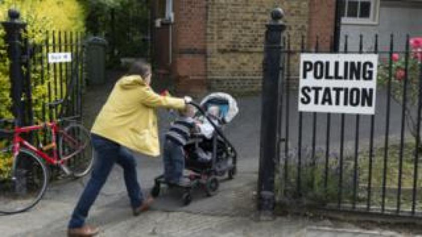 A voting mother arrives with children at a polling station