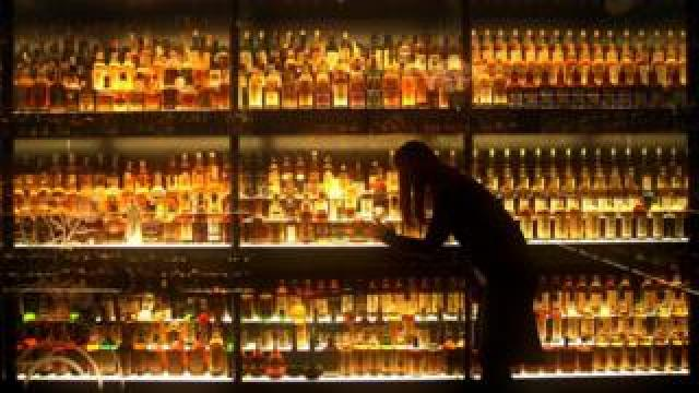 A woman examines bottles of Scotch whisky on a set of shelves