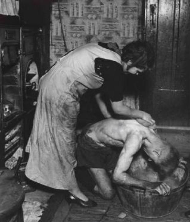 A photograph of a woman helping a man bathe in a tin bath