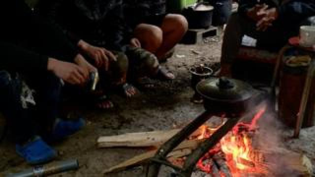 Vietnamese migrants sit around a fire at a camp in France