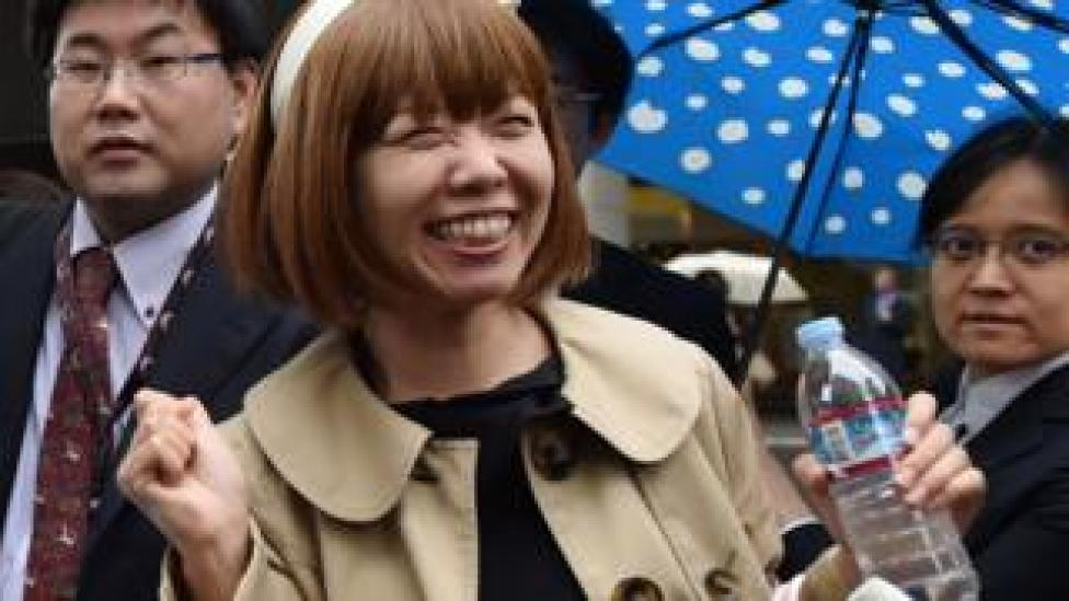 Japanese artist Megumi Igarashi smiles as she speaks to reporters in front of the Tokyo District Court on May 9, 2016.
