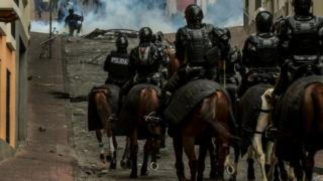 About 10 police on horseback marching through the hilly streets of Quito