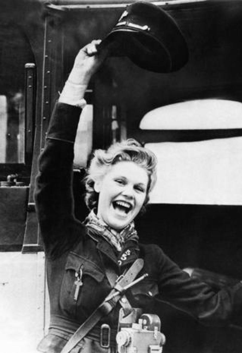 A woman bus conductor waves her hat in celebration