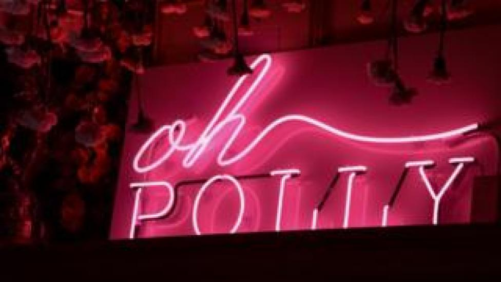 A pink fluorescent sign of the Oh Polly logo against a black backdrop.