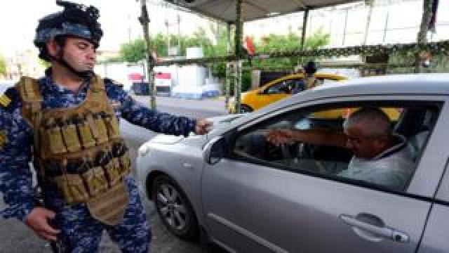 Iraqi police officer checks the identity papers of a driver in Baghdad's Karada district (12 May 2019)