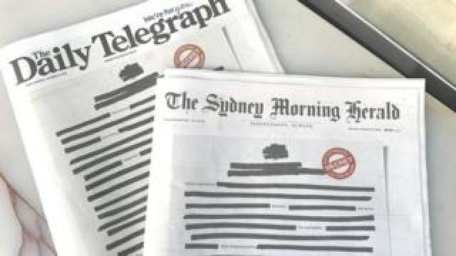 Copies of The Daily Telegraph and The Sydney Morning Herald newspapers feature blacked-out text