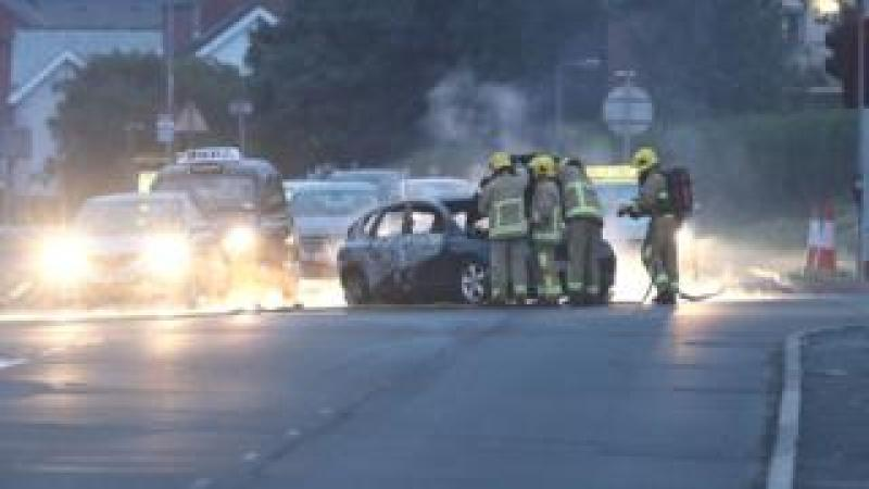 Fire fighters tackle a car on fire in Dundonald