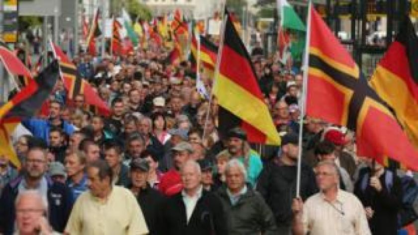 Supporters of the Pegida movement march through Dresden with German flags on 27 July, 2015.
