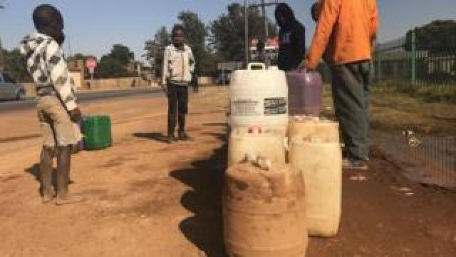 Residents collect water from in Koster
