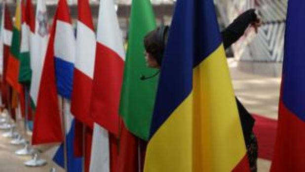 A worker leans through flags to direct people as EU leaders arrive at the Council of the European Union ahead of an EU Council meeting on April 29, 2017 in Brussels